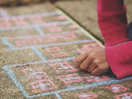 A hand of a child drawing a hopscotch outline