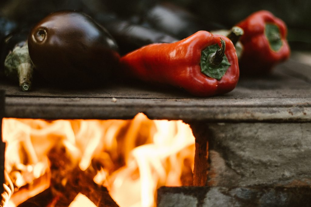 Eggplants and peppers roasted on a stove with an open flame